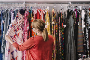Woman looking at dress hanging on rack while standing at store - MASF03855