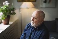 Thoughtful senior man looking away at home - MASF03864