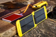 Smart phone being charged by solar charger at campsite - MASF03873