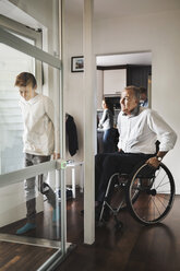 Son and father entering wheelchair lift at home - MASF03876