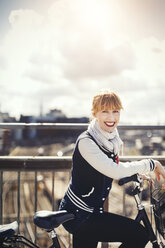 Side view portrait of happy businesswoman standing with bicycle on bridge against sky - MASF03879