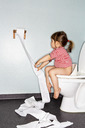 Side view of girl removing paper while sitting on toilet - MASF03882
