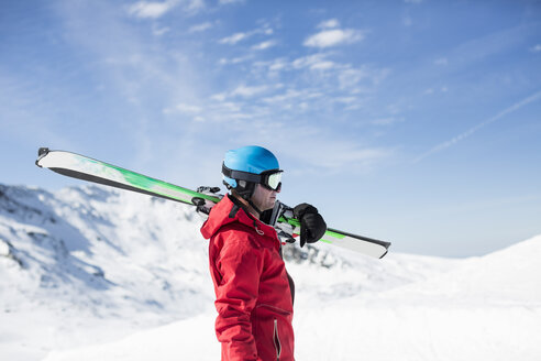 Side view of man carrying skis on snowy mountain - MASF03891