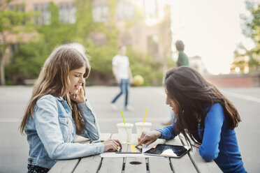 Side view of female teenagers using digital tablet at table outdoors - MASF03900