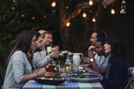 Side view of happy multi-ethnic friends having dinner at table in yard - MASF03915