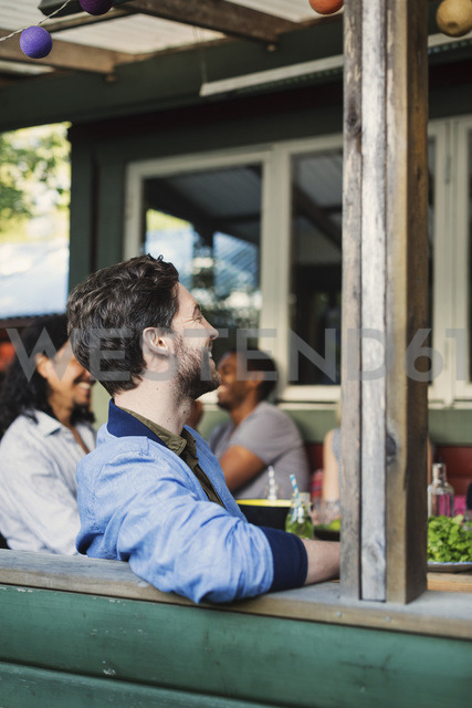 Side view of happy man sitting at porch while enjoying summer party with friends - MASF03918