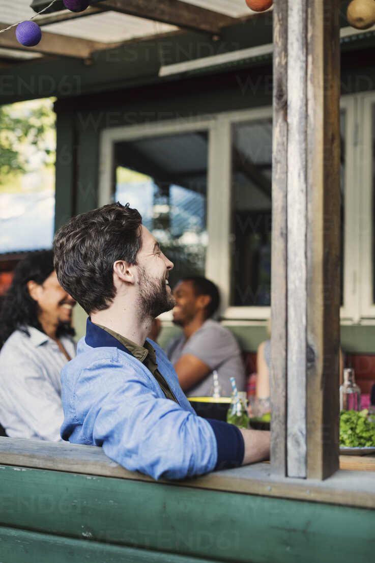 Side view of happy man sitting at porch while enjoying summer party with friends - MASF03918 - Maskot ./Westend61