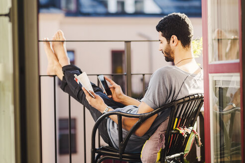 Side view of man using smart phone while holding guidebook at balcony - MASF03924