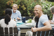 Side view portrait of happy man enjoying meal with family at outdoor table - MASF03927