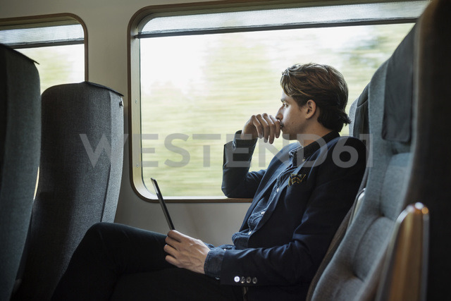 Side view of thoughtful businessman holding digital tablet in train - MASF03939 - Maskot ./Westend61
