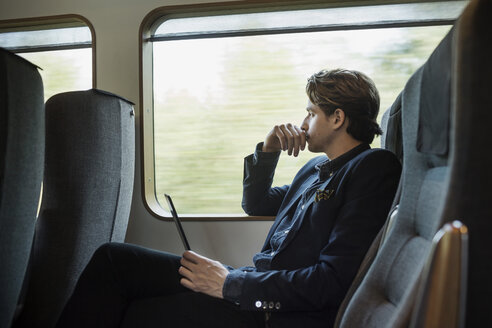 Side view of thoughtful businessman holding digital tablet in train - MASF03939