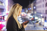 Side view of woman using smart phone on bridge in city at night - MASF03948