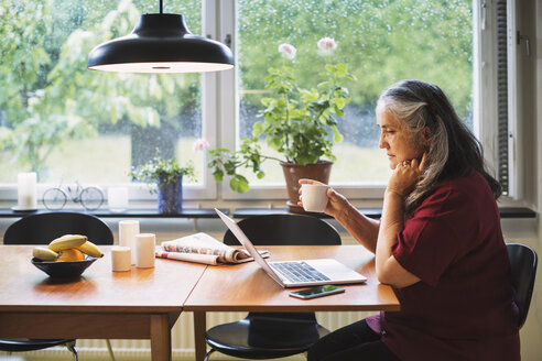 Side view of senior woman using laptop while having coffee at table - MASF03957