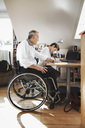 Side view of disabled man looking at son studying at home - MASF03960
