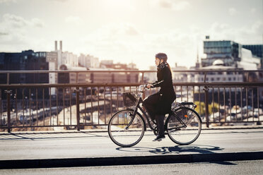 Side view of businesswoman riding bicycle on bridge in city - MASF03963