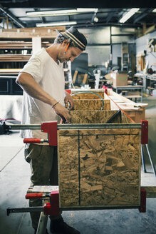 Side view of carpenter making furniture at workshop - MASF03969
