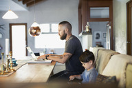 Side view of father and son using technologies at dining table - MASF03981