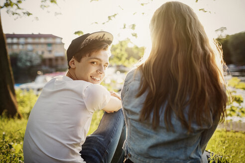 Rear view portrait of happy teenager sitting with female friend at lakeshore - MASF03990