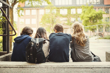 Rear view of teenagers sitting on steps outdoors - MASF03996