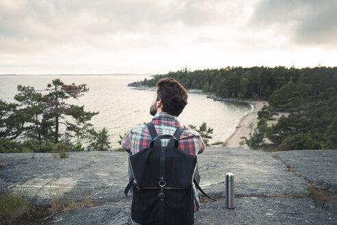 Rear view of wonderlust man sitting on rock at lakeshore - MASF04014