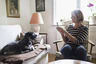 Senior woman photographing dog through smart phone at home - MASF04026