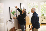 Senior man looking at woman hanging picture frame at home - MASF04032