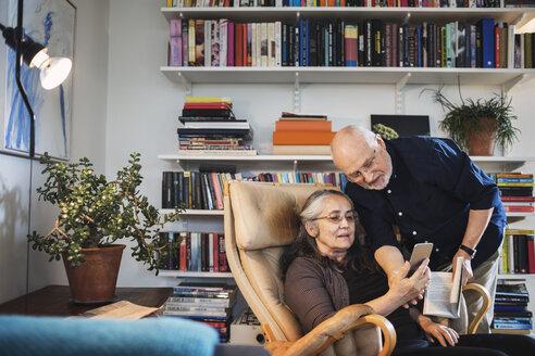 Senior couple using mobile phone at home - MASF04035