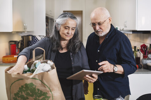 Senior couple with grocery bag using digital tablet in kitchen - MASF04038