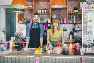 Portrait of male and female baristas standing at cafe counter - MASF04041