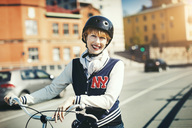 Portrait of happy woman standing with bicycle on city street - MASF04047
