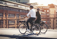 Rear view of business people riding bicycles on bridge - MASF04050