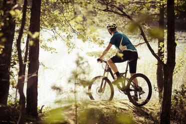 Rear view of cyclist at lakeshore - MASF04080