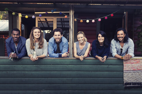 Portrait of multi-ethnic friends standing on porch at log cabin - MASF04083