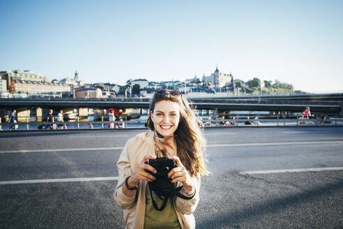 Portrait of happy tourist holding camera on bridge against clear sky - MASF04086