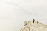 Rear view of family walking on pier at sea against sky - MASF04089