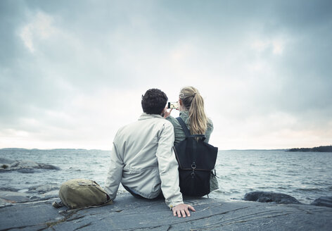 Rear view of couple taking selfie while sitting on rock by sea - MASF04095