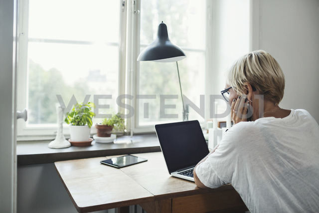 Rear view of industrial designer using laptop at home office - MASF04101