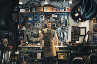 Portrait of confident mechanic leaning on workbench - MASF04110