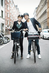 Portrait of happy business people with bicycles standing on city street - MASF04113