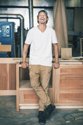 Portrait of carpenter laughing while standing at workshop - MASF04119