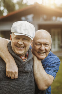 Portrait of happy gay man leaning on partner's shoulders at yard - MASF04122