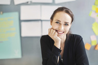 Portrait of confident businesswoman smiling with hand on chin in office - MASF04125