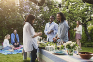 Multi-ethnic friends preparing food at dining table in backyard - MASF04134