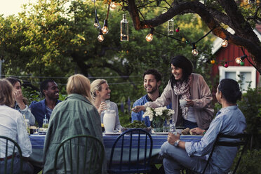 Multi-ethnic friends enjoying dinner party at yard - MASF04140