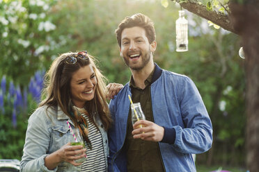 Portrait of happy man enjoying with woman while holding drink bottles at summer party - MASF04143