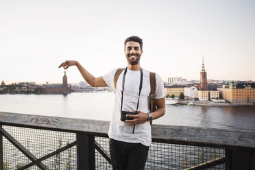 Optical illusion of happy male tourist holding building in city against clear sky - MASF04146
