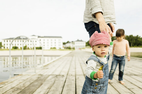 Portrait of baby girl standing with family on pier at beach against clear sky - MASF04149