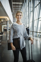 Portrait of confident businesswoman with luggage standing at airport - MASF04152