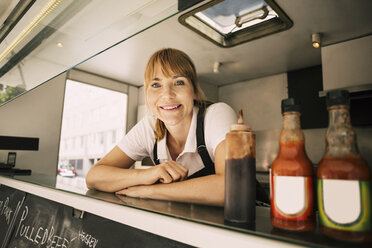 Portrait of happy female chef leaning on counter at food truck - MASF04158