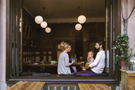 Mid adult parents with son in restaurant seen through window - MASF04188